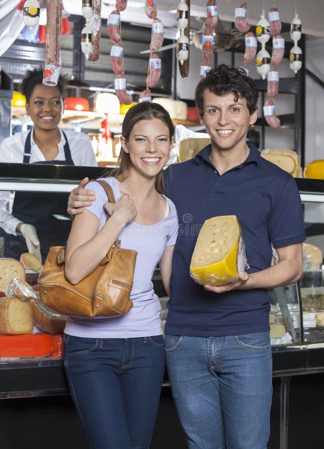 Szczęśliwy potomstwo pary mienia ser Przy sklepem spożywczym fotografia royalty free