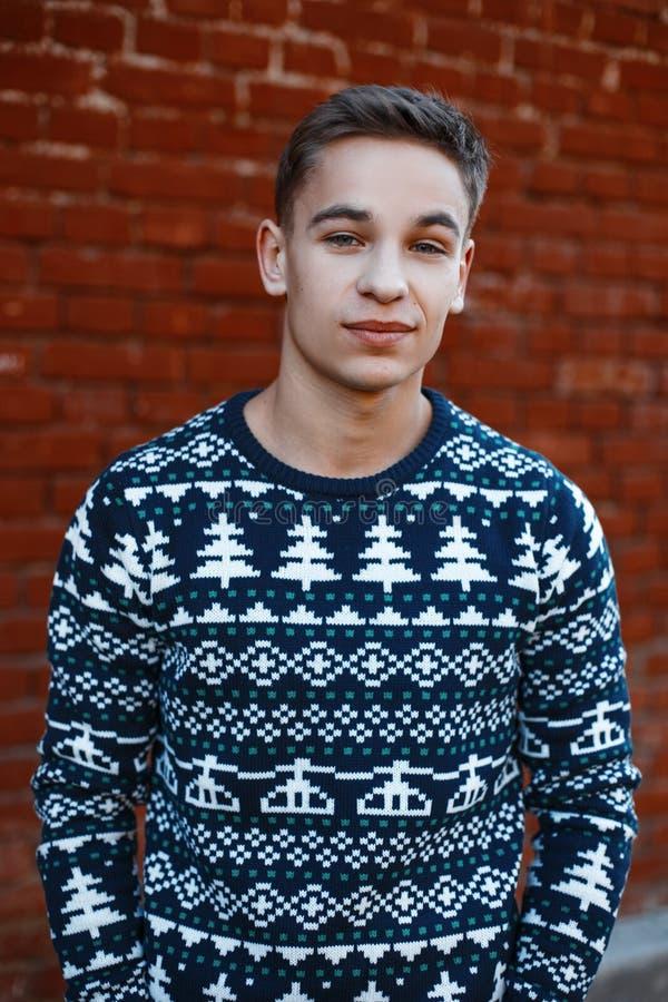 Szczęśliwy powabny śliczny młody człowiek w trykotowym ciepłym rocznika pulowerze z Bożenarodzeniowym ornamentu stojakiem na ulic zdjęcia royalty free