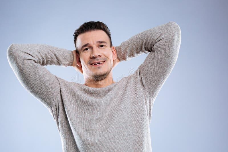 Szczęśliwy pozytywny ładny mężczyzna dotyka jego kierowniczego obrazy stock