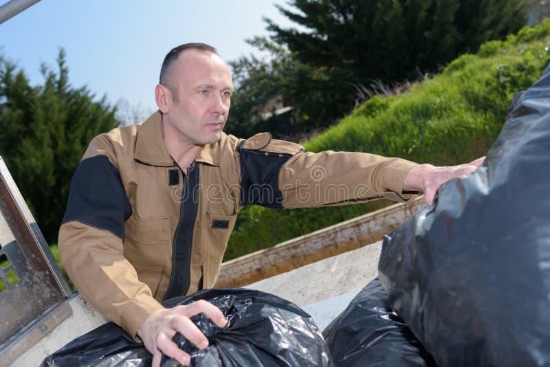 Szczęśliwy pracujący trwanie pobliski kosz na śmiecie obrazy stock