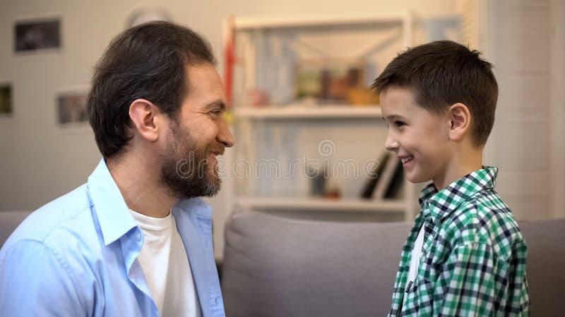 Szczęśliwy preschool syn i ojciec ono uśmiecha się patrzejący each inny, rodzina, miłość obraz stock