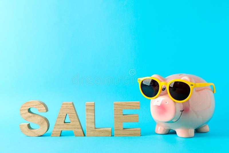 Szczęśliwy prosiątko bank z okularami przeciwsłonecznymi i wpisową sprzedażą na koloru tle, przestrzeń dla teksta zdjęcia stock