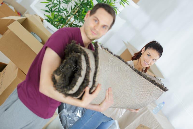 Szczęśliwy przewożenie staczający się potomstwo pary dywan obrazy stock