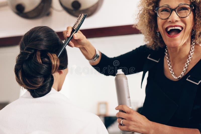Szczęśliwy przyglądający włosiany stylista pracuje przy salonem obrazy stock