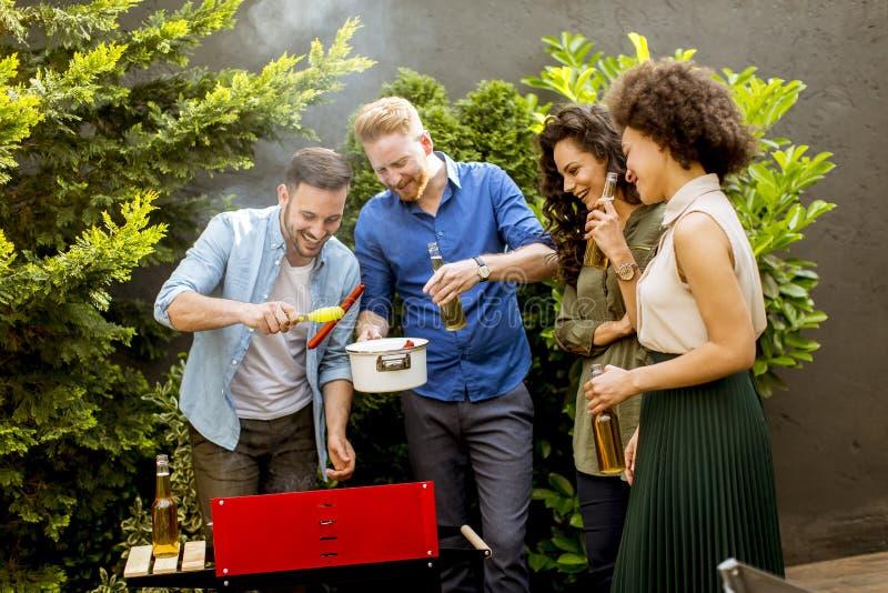 Szczęśliwy przyjaciół piec na grillu karmowy outdoors i cieszyć się grilla przyjęcia zdjęcia royalty free