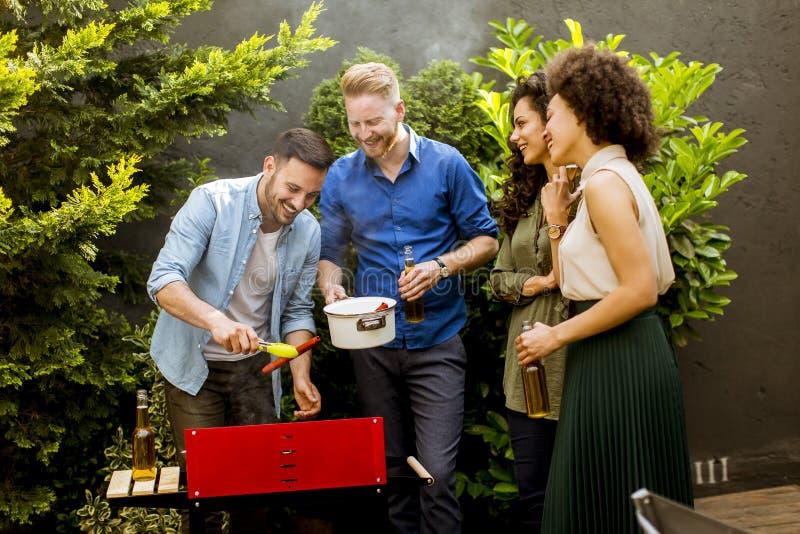 Szczęśliwy przyjaciół piec na grillu karmowy outdoors i cieszyć się grilla przyjęcia obraz royalty free