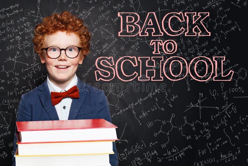 Szczęśliwy przystojny dziecko uśmiecha się książki na chalkboard tle i trzyma tylna koncepcji do szko?y zdjęcia stock