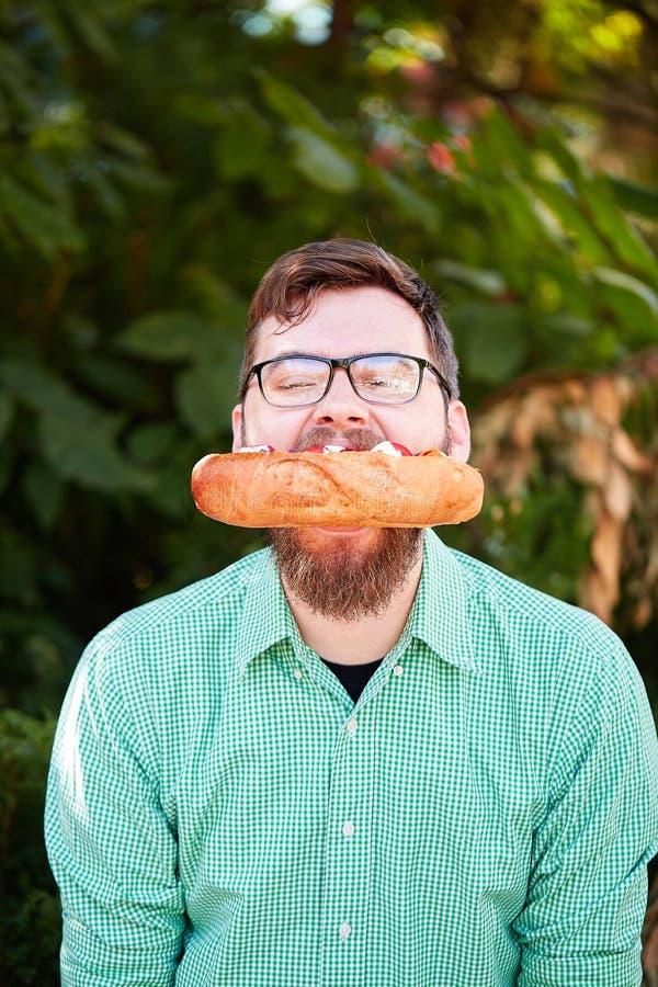 Szczęśliwy przystojny mężczyzna je hot dog na naturalnym tle Fasta food pojęcie kosmos kopii fotografia stock