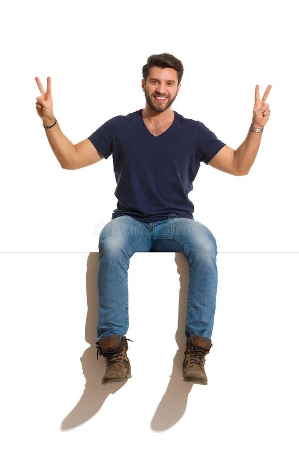 Szczęśliwy Przystojny mężczyzna Siedzi Na wierzchołku I Pokazuje pokój ręki znaka zdjęcia stock
