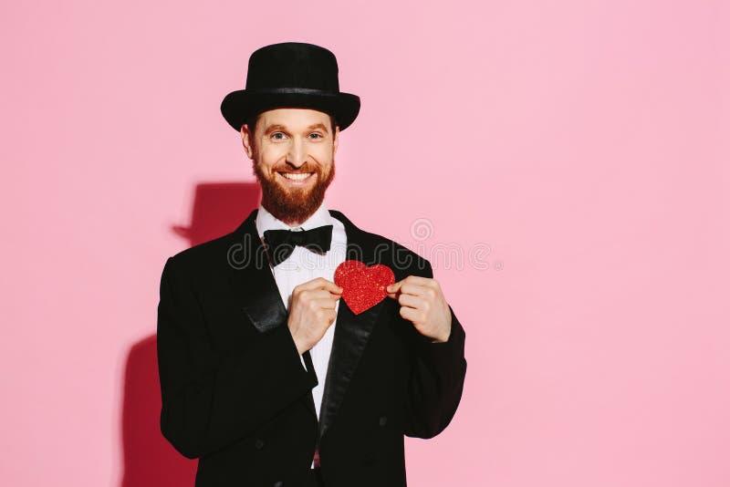 Szczęśliwy przystojny mężczyzna trzyma jego serce w jego ręki zdjęcie stock