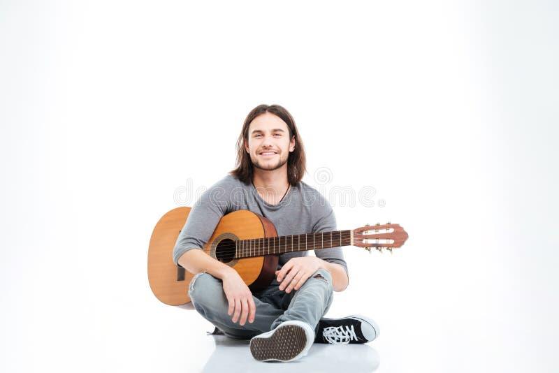 Szczęśliwy przystojny młodego człowieka obsiadanie na podłoga z gitarą obraz stock
