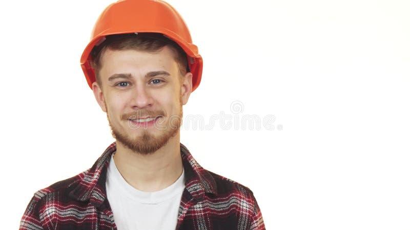 Szczęśliwy przystojny młody pracownik budowlany ono uśmiecha się będący ubranym hardhat zdjęcia royalty free