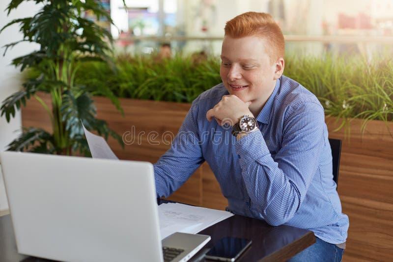 Szczęśliwy przystojny ufny biznesmen z czerwonym włosy ubierał w sprawdzać koszulowym obsiadaniu przy stołem przed otwartym lapto fotografia royalty free