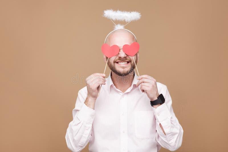 Szczęśliwy przystojny w średnim wieku łysy brodaty anioł w białym koszulowym sta zdjęcia royalty free
