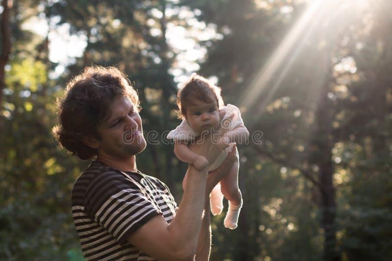 Szczęśliwy radosny ojciec ma zabawę rzuca jego dziecka w powietrzu przeciw zmierzchu tłu - intencjonalny słońca świecenie i zdjęcia royalty free