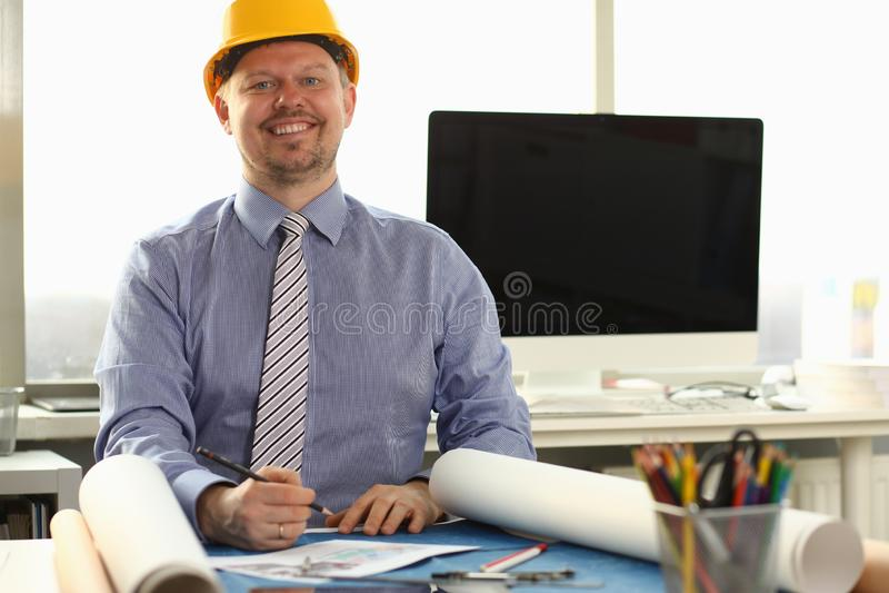 Szczęśliwy robociarz Kreśli budynku projekt przy biurkiem zdjęcie stock
