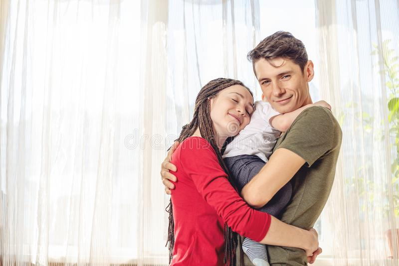 Szczęśliwy rodzica ojciec i matka bawić się z dziecko synem przy dalej nadokiennym tłem Rozochocona i nowożytna młoda rodz zdjęcia stock
