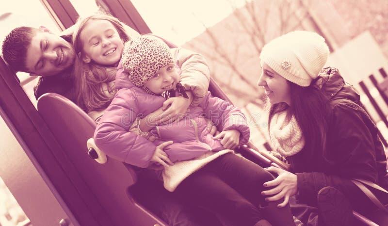Szczęśliwy rodzina składająca się z czterech osób przy dziecka ` s boiskiem zdjęcie stock