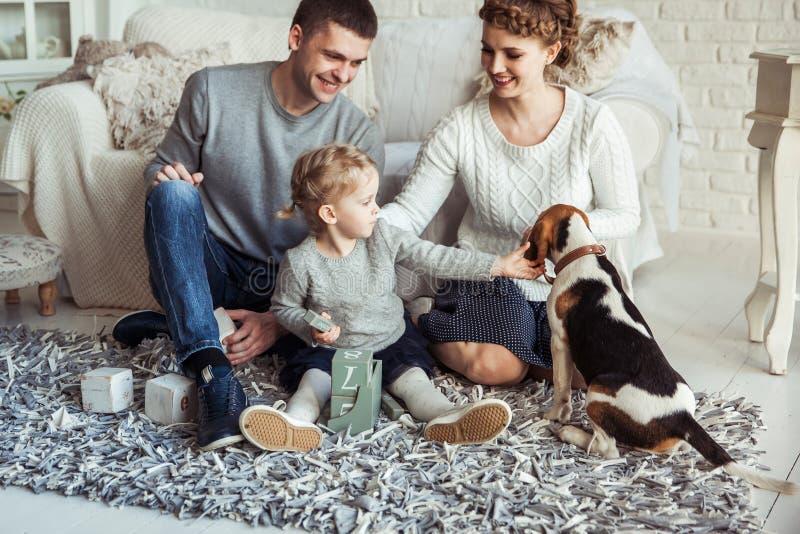 Szczęśliwy rodzinny bawić się z zwierzę domowe psem w przestronnym żywym pokoju zdjęcia royalty free