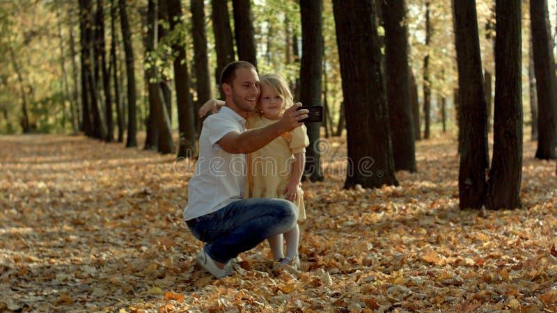 Szczęśliwy rodzinny bierze selfie z smartphone w jesień parku zdjęcia stock