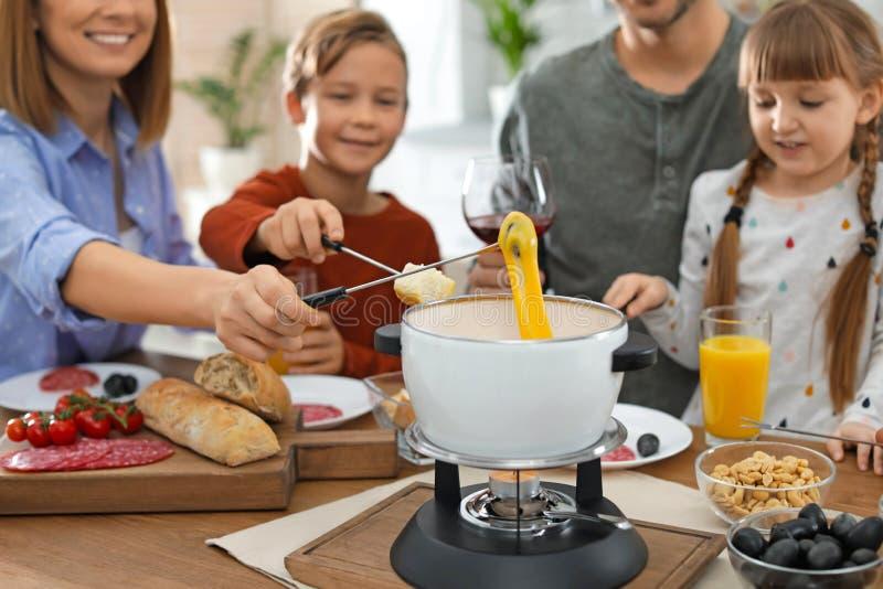 Szczęśliwy rodzinny cieszy się fondue gość restauracji w domu zdjęcia stock