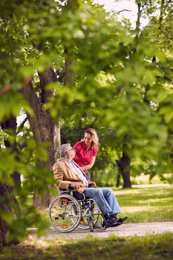 Szczęśliwy rodzinny czas starszych osob mężczyzna opowiada z daught w wózku inwalidzkim obraz stock