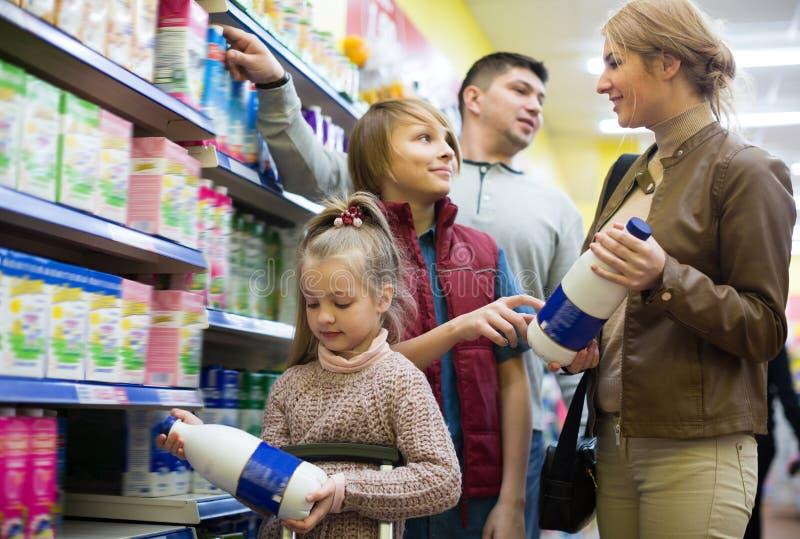 Szczęśliwy rodzinny kupienie pasteryzujący mleko zdjęcia royalty free