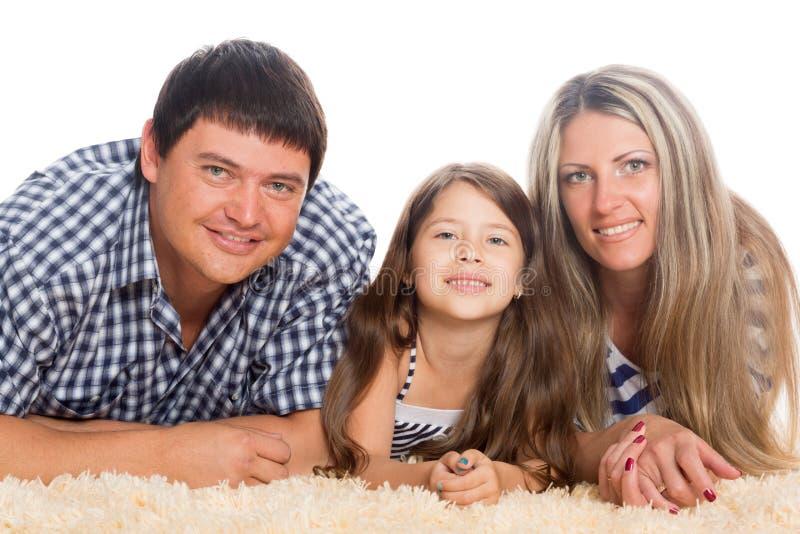 Szczęśliwy rodzinny lying on the beach na dywaniku obrazy stock