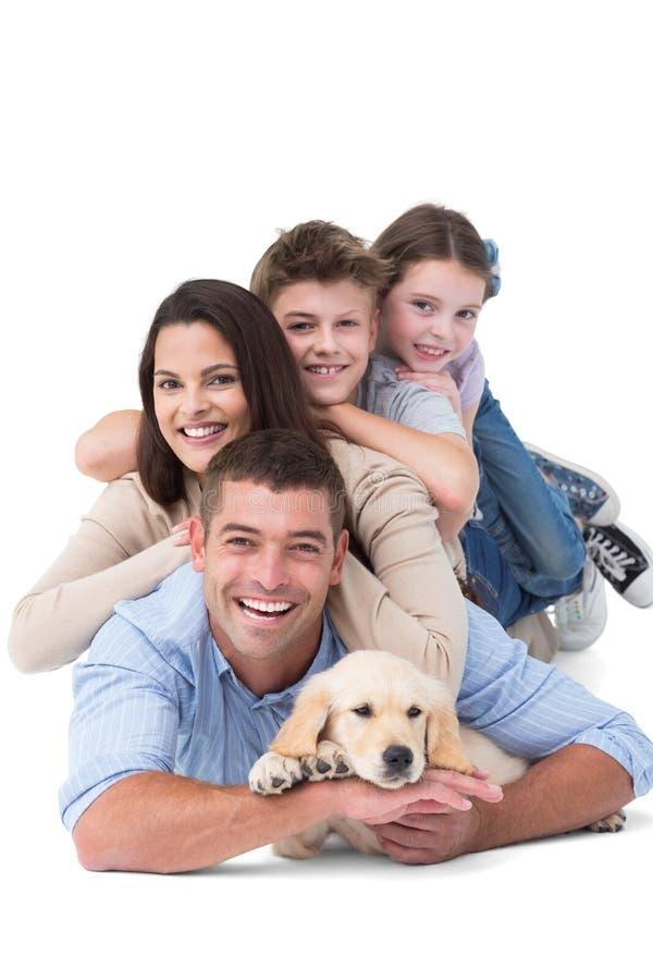 Szczęśliwy rodzinny lying on the beach na górze each inny z psem obraz stock