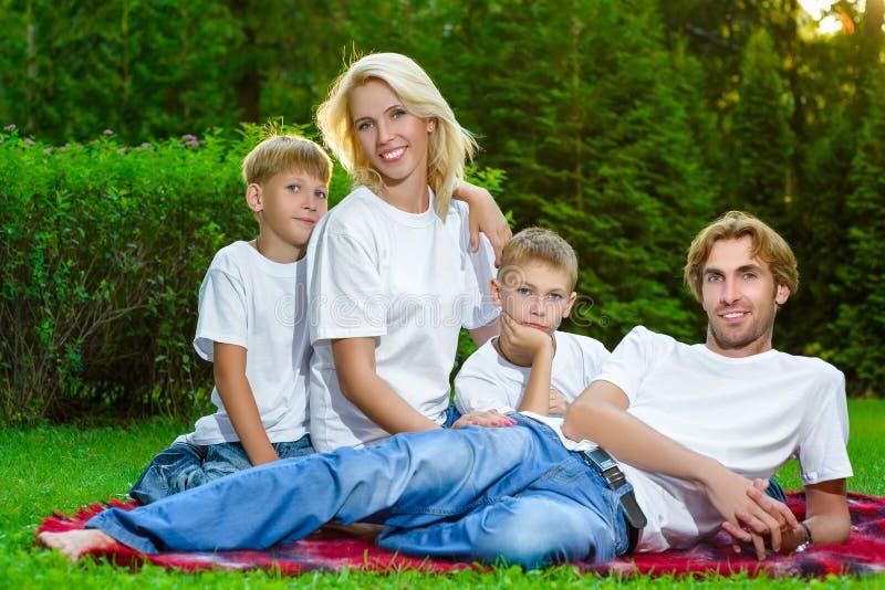 Szczęśliwy rodzinny lying on the beach na trawie w lecie piknik obraz stock