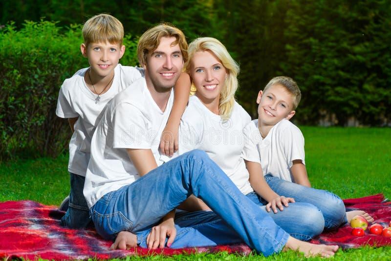 Szczęśliwy rodzinny lying on the beach na trawie w lecie piknik zdjęcie stock