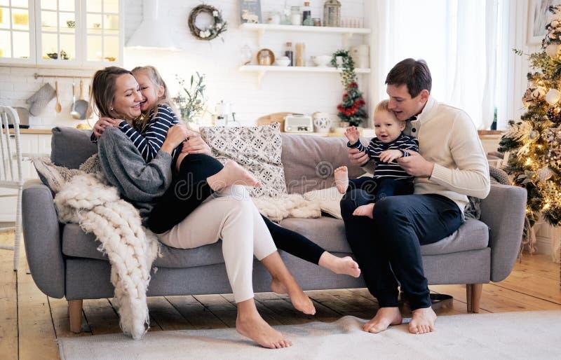 Szczęśliwy rodzinny mieć zabawę w sypialni Rozochocona młoda rodzina z dzieciakami siedzi na kanapie obrazy royalty free