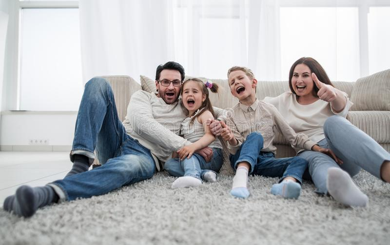 Szczęśliwy rodzinny obsiadanie na dywanie w żywym pokoju zdjęcia royalty free