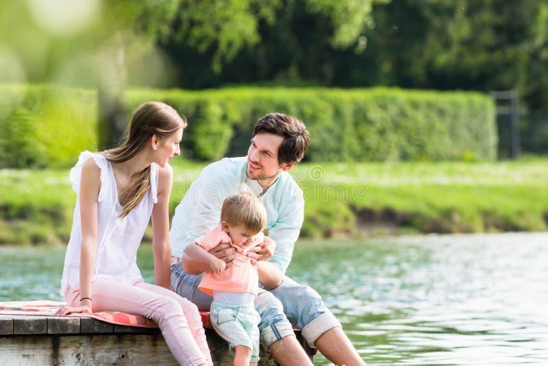 Szczęśliwy rodzinny obsiadanie na jetty na jeziorze lub stawie zdjęcia stock