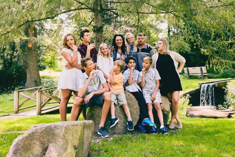Szczęśliwy rodzinny obsiadanie na kamieniach i komunikować zdjęcie royalty free