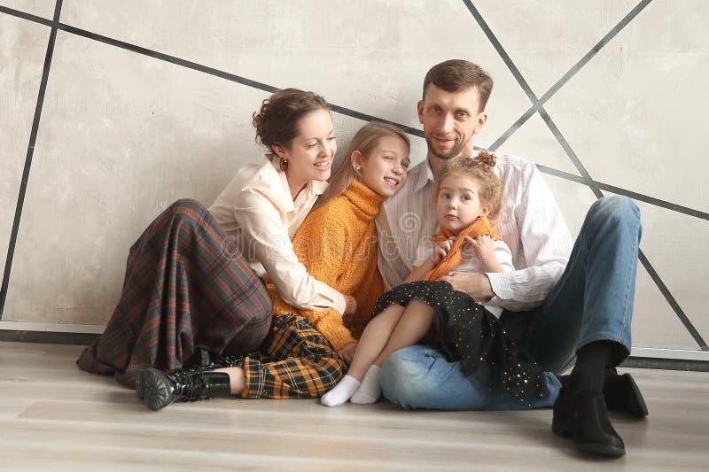 Szczęśliwy rodzinny obsiadanie na podłodze w nowym domu na wigilii obrazy stock