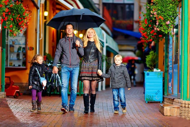 Szczęśliwy rodzinny odprowadzenie pod deszczem na kolorowej ulicie fotografia stock