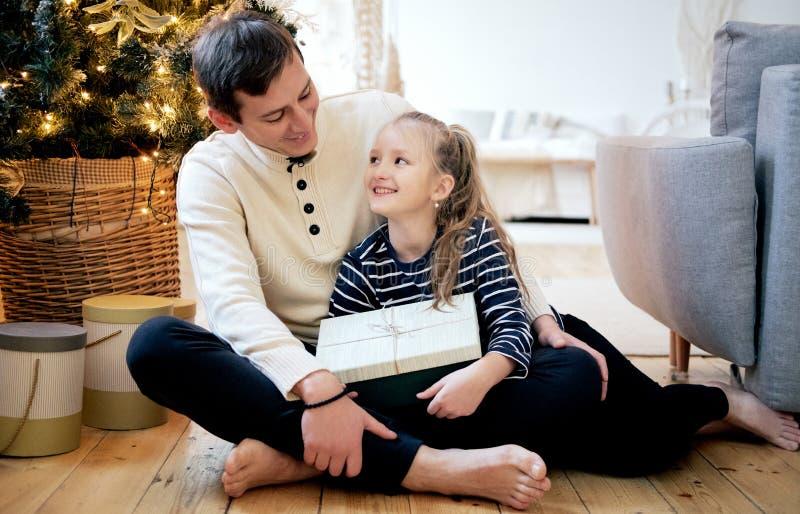 Szczęśliwy rodzinny ojca i córki obsiadanie na podłodze przy wigilią zdjęcia stock