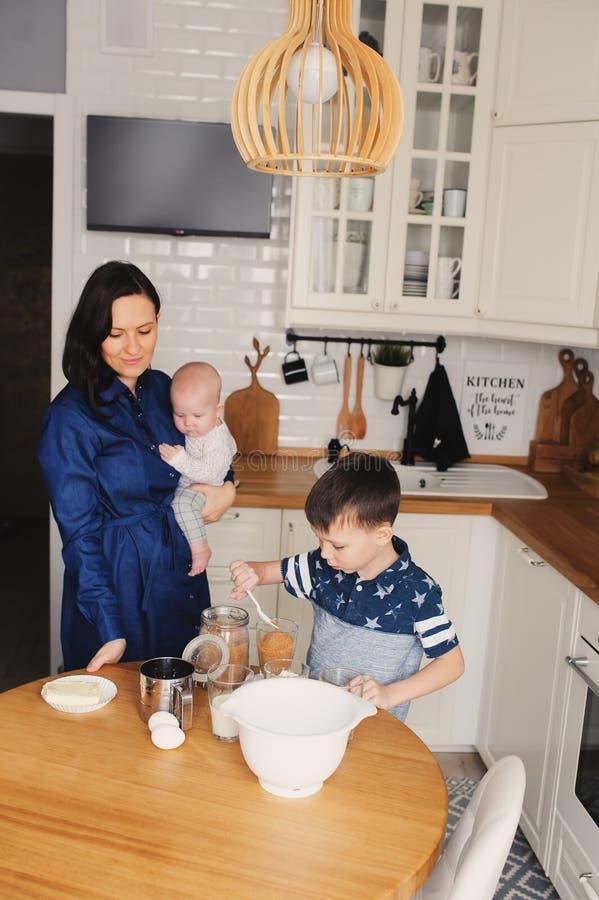 Szczęśliwy rodzinny pieczenie w nowożytnej białej kuchni wpólnie Matki, syna i dziecka córki kucharstwo w wygodnym weekendowym ra zdjęcie stock