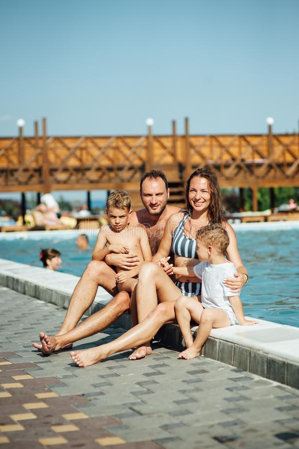 Szczęśliwy rodzinny przytulenie blisko basenu przy zmierzchem zdjęcie stock