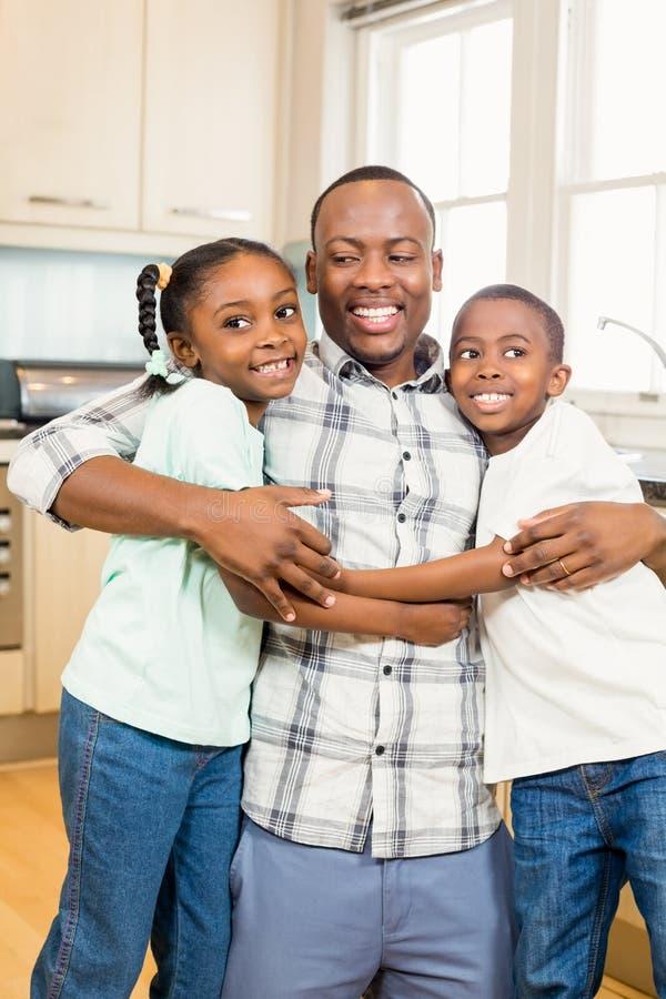 Szczęśliwy rodzinny przytulenie w kuchni obraz stock