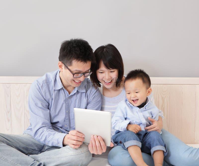 Szczęśliwy rodzinny używa pastylka komputer osobisty zdjęcia royalty free