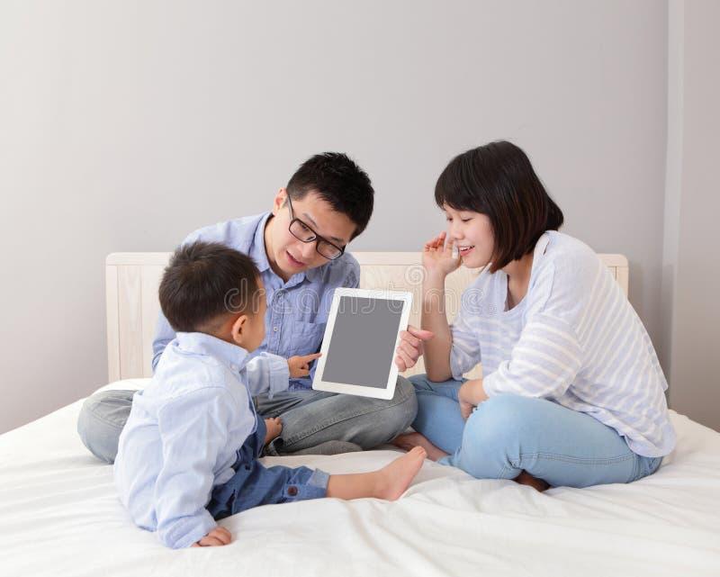 Szczęśliwy rodzinny używa pastylka komputer osobisty zdjęcie stock