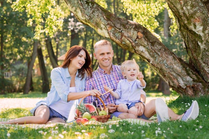 Szczęśliwy rodzinny wydaje czas w parku z synem trzyma precla zdjęcie royalty free