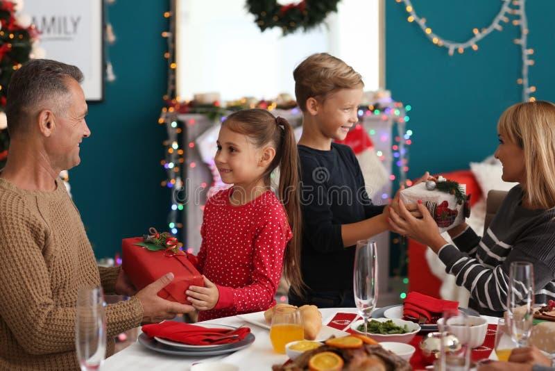 Szczęśliwy rodziny dawać each podczas Bożenarodzeniowego gościa restauracji inne teraźniejszość w domu zdjęcie royalty free