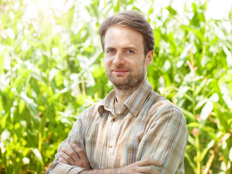 Szczęśliwy rolnik przed jego kukurydzanym polem zdjęcie stock