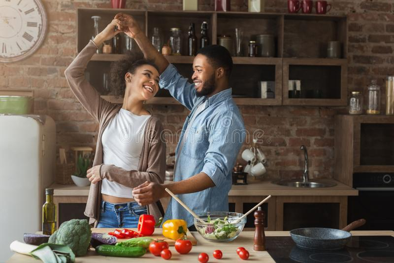 Szczęśliwy romantyczny para taniec w kuchni podczas gdy gotujący obraz royalty free