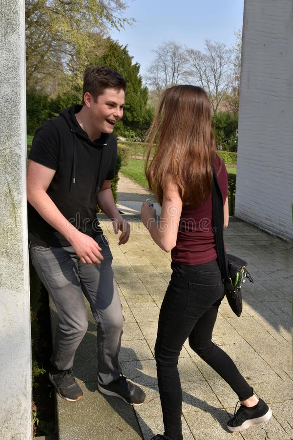 Szczęśliwy roześmiany nastoletni chłopak spotyka jego dziewczyny zdjęcia royalty free