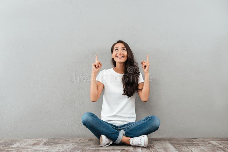 Szczęśliwy rozochocony azjatykci kobiety obsiadanie na podłoga zdjęcia stock