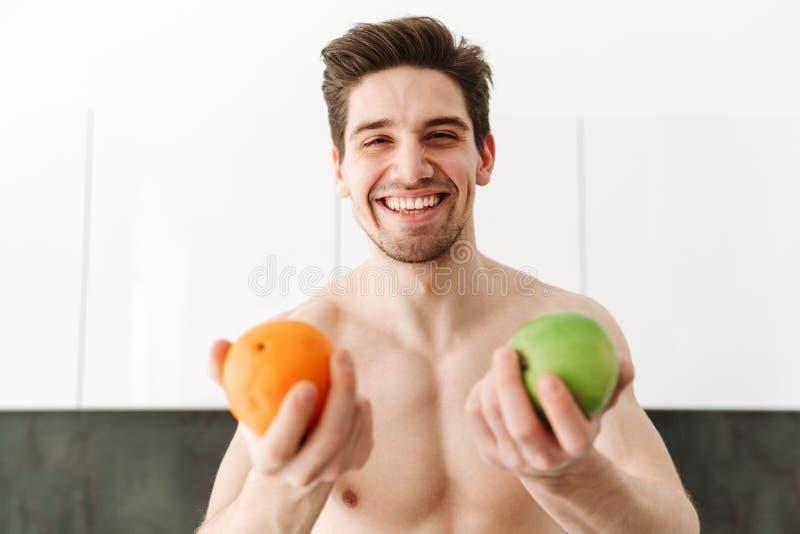 Szczęśliwy rozochocony nagi mężczyzna sportowiec pokazuje pomarańcze i jabłka zdjęcie stock